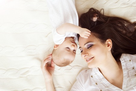 Cute little baby girl and her mother lying on a knitted blanket. photo