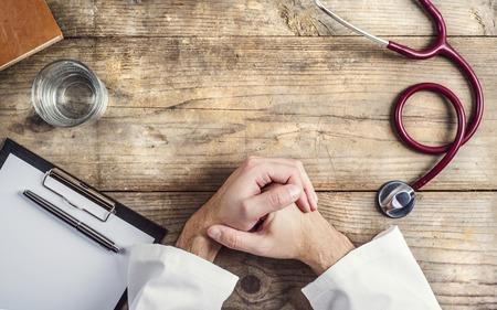 Handen van onherkenbare arts gelegd op een tafel. Houten bureau achtergrond.