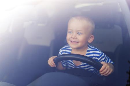 asiento coche: Ni�o jugando con un volante en un coche