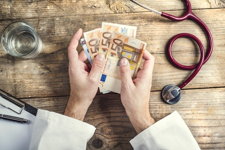 accepting: Hands of unrecognizable doctor accepting a bribe. Wooden desk background. Stock Photo