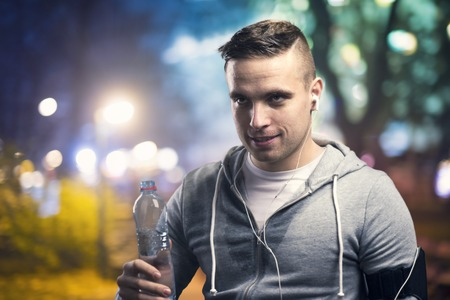 night shirt: Young sportsman jogging in the night city with a water bottle