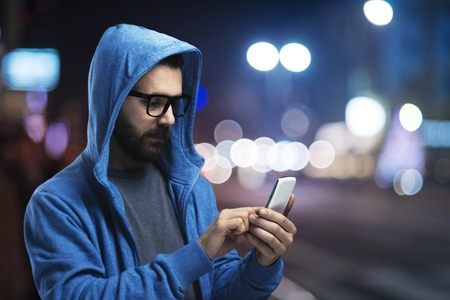 people street: Handsome young hipster with his smartphone outside in the night city
