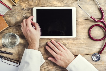 red stethoscope: Hands of unrecognizable doctor writing on a tablet. Wooden desk background.