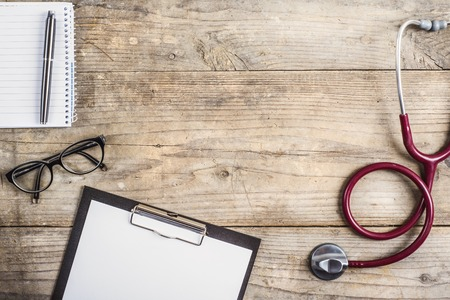 Workplace of a doctor. Stethoscope, clip board, glasses and other things on wooden desk background.