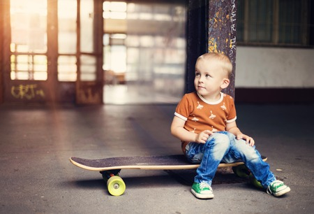 boy jeans: Cute little boy with his skateboard on a walk in the city