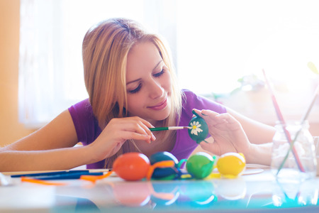 creative egg painting: Beautiful young woman hand painting easter eggs Stock Photo