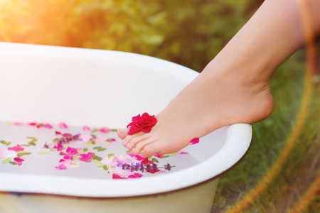 baño: Mujer joven hermosa que toma un baño de hierbas.