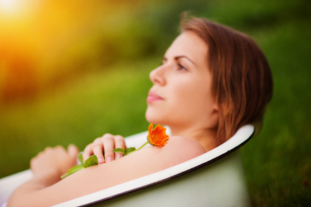 garden marigold: Beautiful young woman taking a herbal bath outside in a green nature.