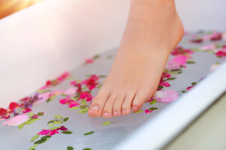 foot spa: Beautiful young woman taking a herbal bath.