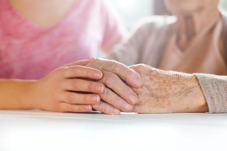 mujeres maduras: Abuela irreconocible y su nieta de la mano. Foto de archivo