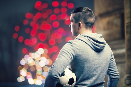 outdoor training: Young sportsman in the night city holding a soccer ball