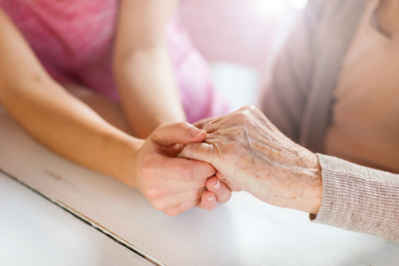 manos agarrando: Abuela irreconocible y su nieta de la mano. Foto de archivo