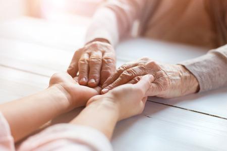 an elderly person: Abuela irreconocible y su nieta de la mano. Foto de archivo
