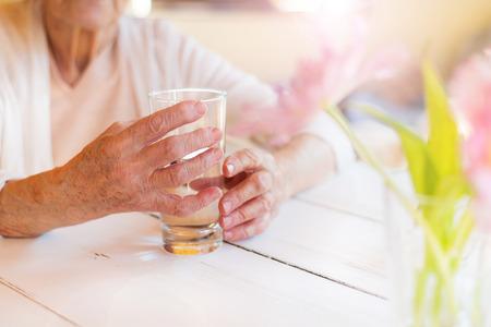 水のガラスを保持して判読不能の年配の女性の手 写真素材
