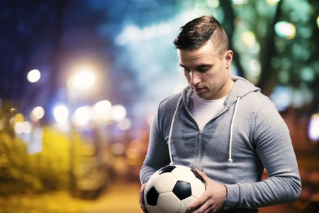 futball: Young sportsman in the night city holding a soccer ball