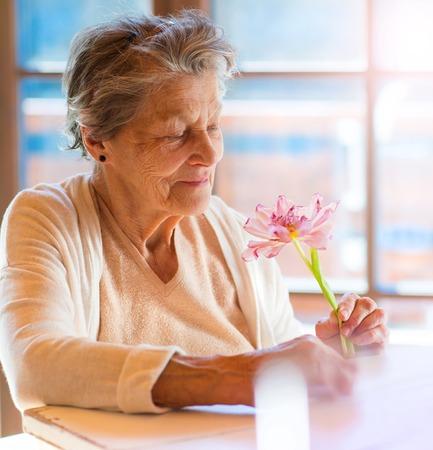 damas antiguas: Mujer mayor hermosa que sostiene una flor rosa.