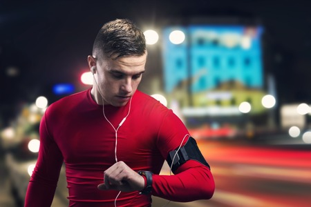 night shirt: Young sportsman jogging in the night city