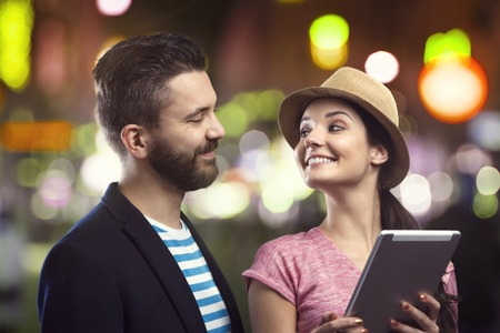 outdoor glamour: Trendy young hipster couple with a tablet enjoying nightlife in the city