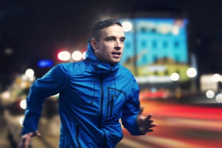 man haircut: Young sportsman jogging in the night city