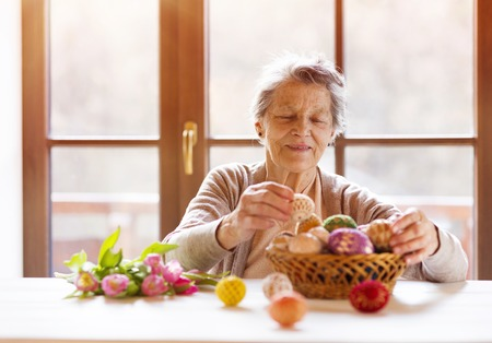 Beautiful senior woman with easter eggs and tulips.