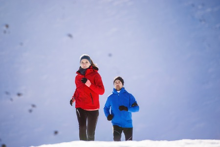 Young couple jogging outside in sunny winter mountains photo