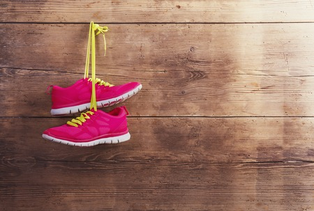 Pair of sneakers hang on a nail on a wooden fence background