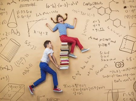 maths: Cute boy and girl learning playfully in frot of a big blackboard. Studio shot on beige background. Stock Photo