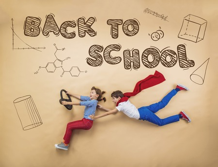 driving school: Cute boy and girl learning playfully in frot of a big blackboard. Studio shot on beige background. Stock Photo