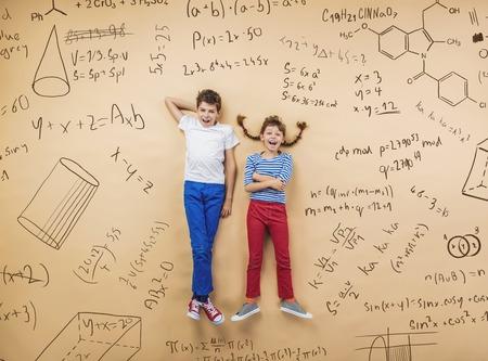 simbolos matematicos: Muchacho lindo y muchacha que aprenden lúdicamente en Frot de una gran pizarra. Estudio tirado en el fondo beige.