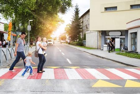Familia joven con dos niños en la ciudad a pie en un paso de peatones Foto de archivo