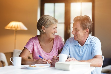 Happy senior couple sitting at the table making plans and drinking coffee in their living room. Stock Photo