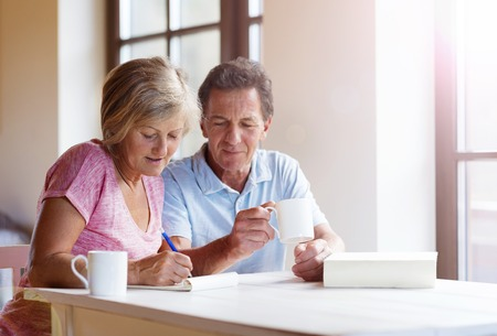 Happy senior couple sitting at the table making plans and drinking coffee in their living room. Archivio Fotografico