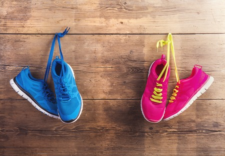 jogging: Two pairs of sneakers hang on a nail on a wooden fence background