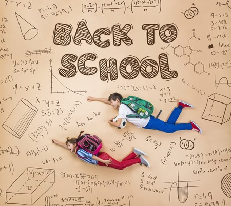 superman: Cute boy and girl learning playfully in frot of a big blackboard. Studio shot on beige background. Stock Photo