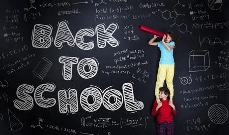 Leuke jongen en meisje leren op speelse wijze in frot van een groot bord. Studio opname op zwarte achtergrond. Stockfoto