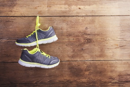 sport background: Pair of sneakers hang on a nail on a wooden fence background