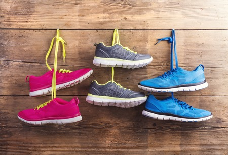 Three pairs of sneakers hang on a nail on a wooden fence background Stock Photo