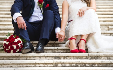 Unrecognizable young wedding couple holding hands as they enjoy romantic moments outside on the stairs