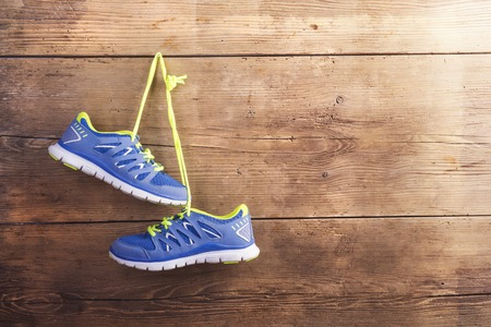 healthy exercise: Pair of sneakers hang on a nail on a wooden fence background