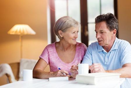 행복 한 고위 커플 계획을 만들고 그들의 거실에서 커피를 마시는 테이블에 앉아.