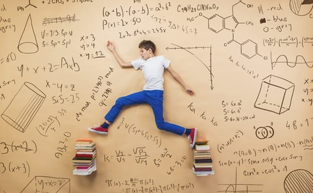 math symbols: Cute little boy learning playfully in frot of a big blackboard. Studio shot on beige background. Stock Photo