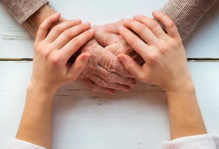 認識できない祖母と孫娘の手を繋いでいます。 写真素材