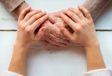 fulfillment: Unrecognizable grandmother and her granddaughter holding hands.