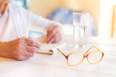 body writing: Hands of unrecognizable senior woman writing on a wooden white desk. Stock Photo