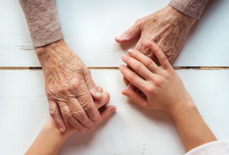 granddaughter: Unrecognizable grandmother and her granddaughter holding hands.
