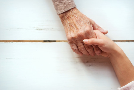 retirement age: Unrecognizable grandmother and her granddaughter holding hands.