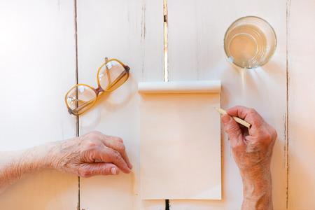 Ruce k nepoznání starší žena psaní na dřevěné bílém stole.