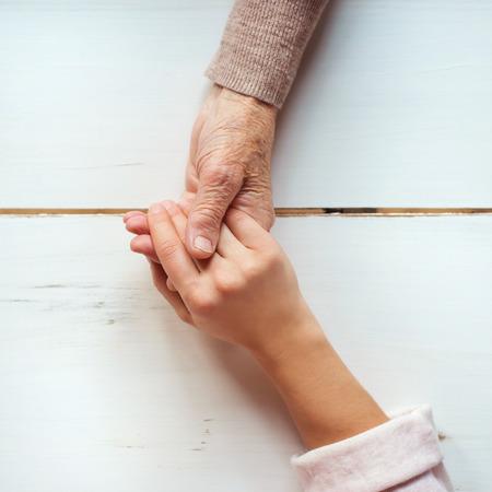 manos entrelazadas: Abuela irreconocible y su nieta de la mano. Foto de archivo
