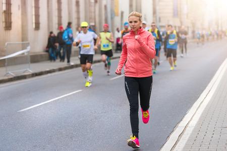 competencia: Joven y bella mujer corriendo en el concurso de la ciudad