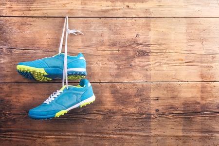 Paar sportschoenen hangen aan een spijker op een houten hek achtergrond Stockfoto
